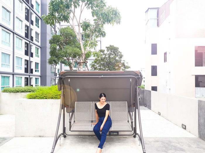 Full length of woman sitting on swing against buildings in city