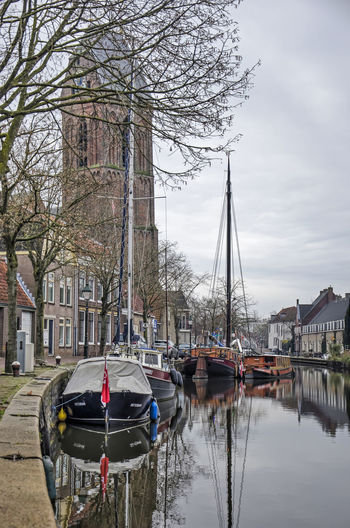 Sailboats in river by buildings against sky