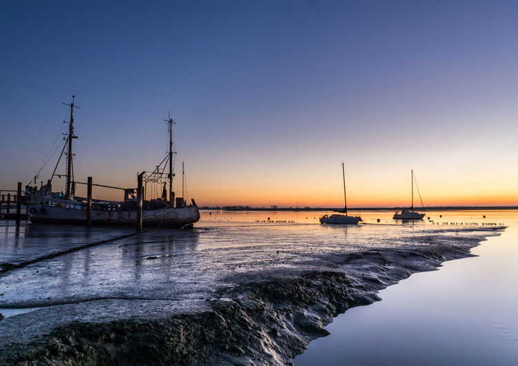 Sailboats moored on sea against clear sky during sunset