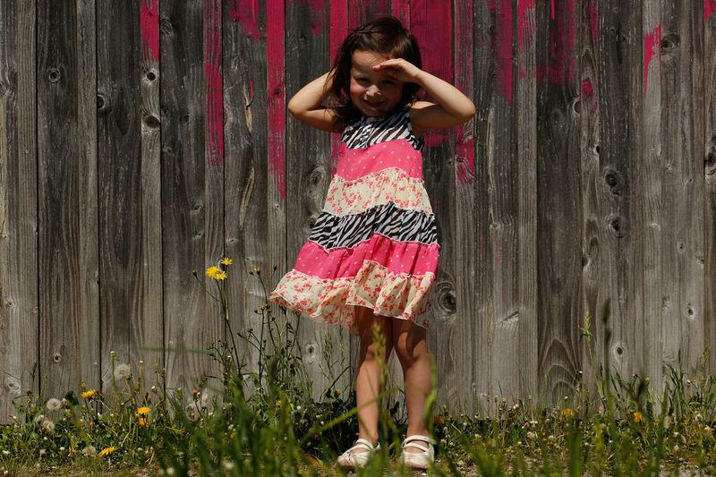 Full length portrait of smiling girl standing in yard against wooden fence
