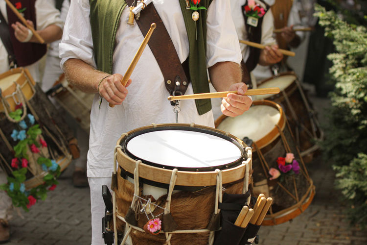 Midsection of people playing drum on street