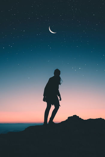 Silhouette woman standing against sky during dusk