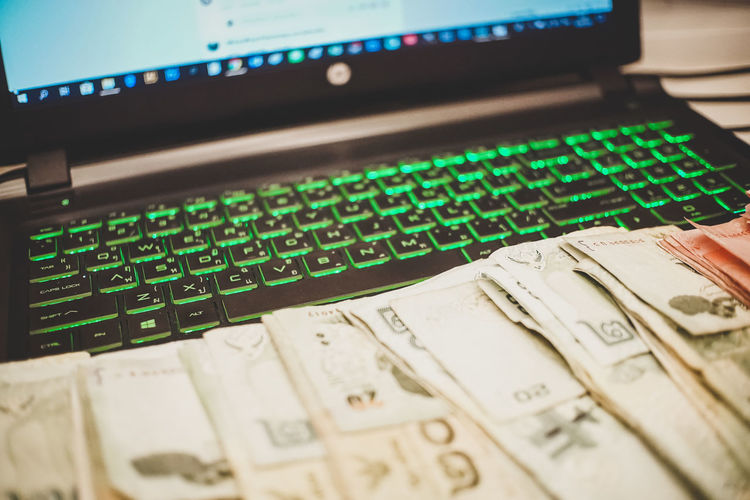 Close-up of laptop and currencies on table
