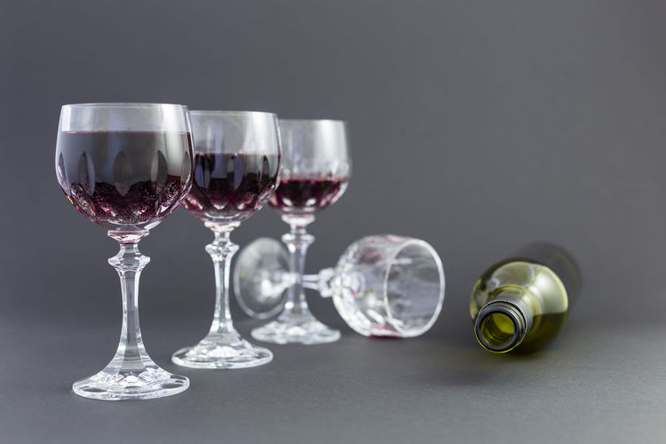 Concept of alcohol consumption, alcoholism and abuse with a line of beautiful crystal glasses filled with red wine, a full and an empty bottle. Stages of drinking underlined by blurred image effect. Drunken Elegant Green Color Objects Red Wine Wine Bottle Abuse Alcohol Alcoholic  Alcoholic Drink Background Black Blurred Background Close-up Drinking Drinking Glass Empty Group Of Objects Leisure Activity No People Red Wine Still Life Studio Shot Wine Wineglass