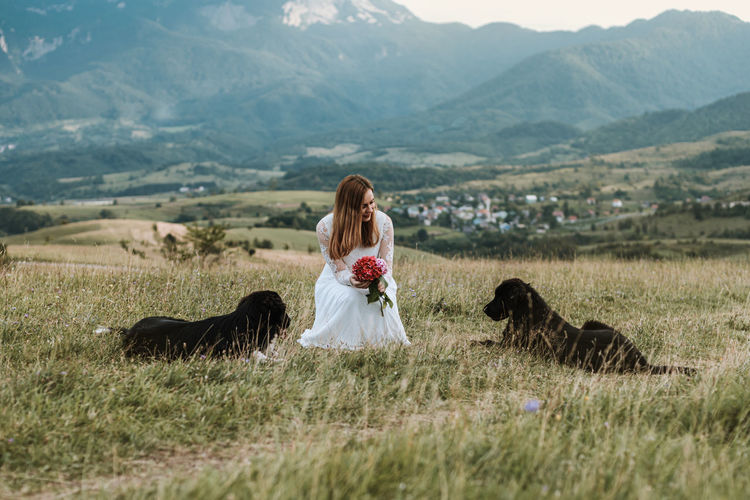 Bride with two wild dogs outdoors in nature