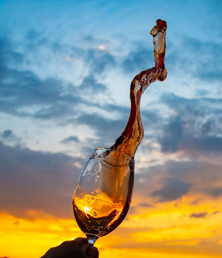 Close-up of frozen splash of wine against sky during sunset