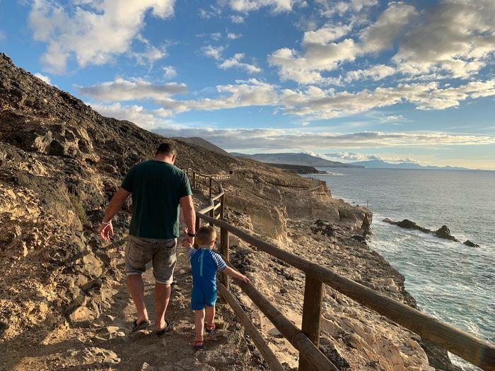 Rear view of man with son walking on rocky coastline by sea