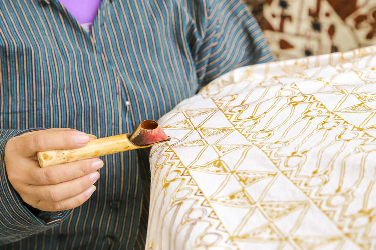 Midsection of woman making batik on textile