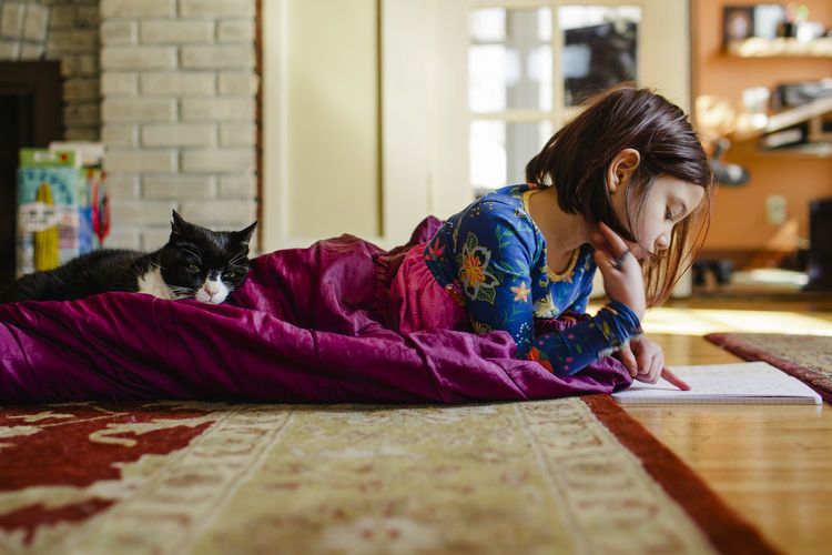 Midsection of woman with cat sitting on floor