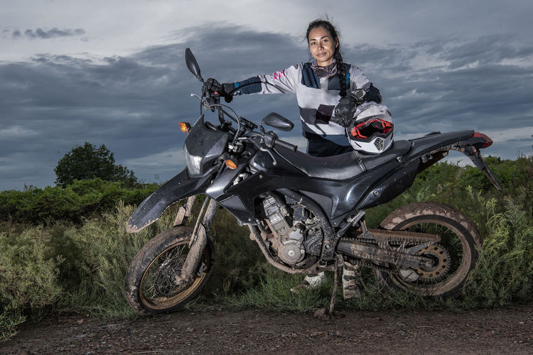 Portrait of woman riding motorcycle against sky