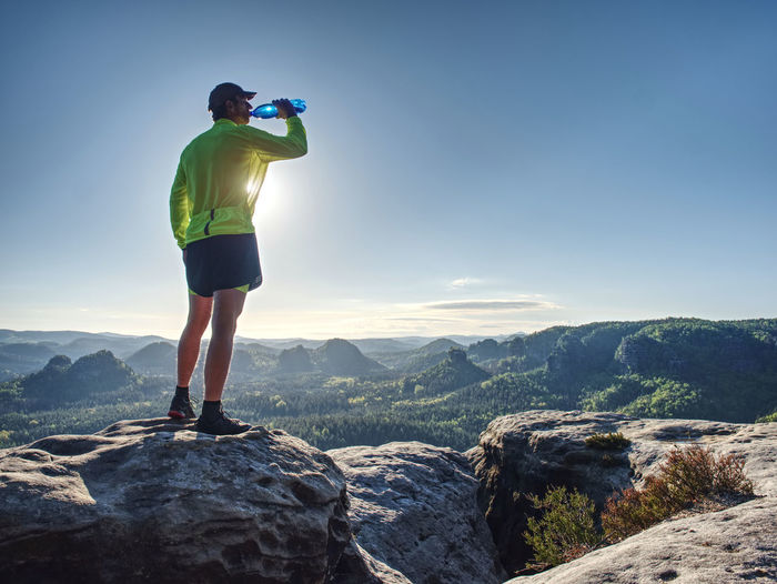 Fit runner in sport suit drinking the water from sport bottle with relax action in morning forest