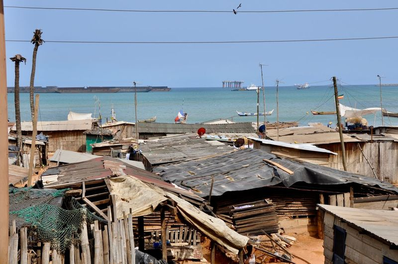 Ghana Shanty Town Tanker Tankers Building Exterior Cable Corrugated Iron Roof Corrugated Roof Fishing Fishing Industry Horizon Over Water Huts Nautical Vessel No People Oil Industry Oil Rig Oil Rig In Background Poverty Roof Sea Shanty Slum Slum Area Transportation Wood - Material