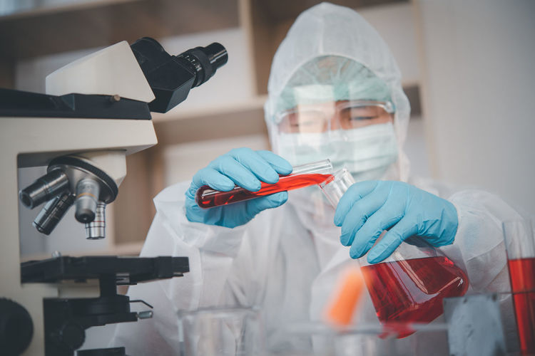 Close-up of doctor examining by microscope