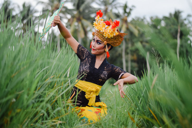 Woman in traditional clothing dancing on grass against sky