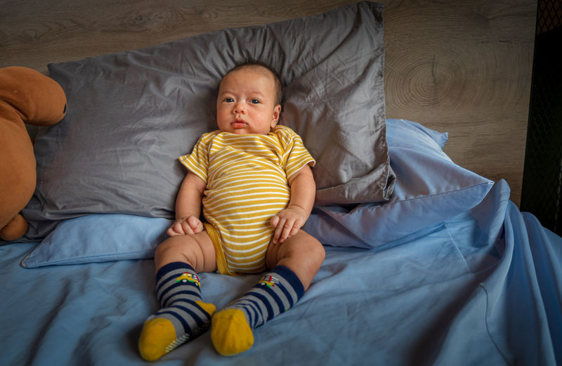 Full length of cute baby relaxing on bed at home