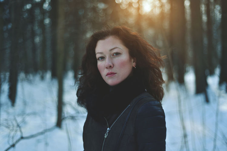 Portrait of young woman standing in forest during winter
