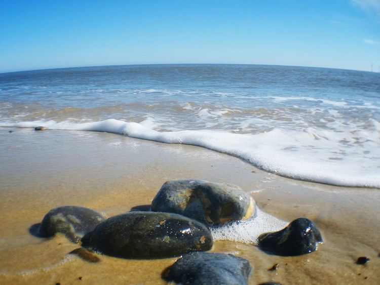 Close Up Pebbles On A Beach Fish Eye Sand Sea Foam Blue Sky The KIOMI Collection Landscapes Pebbles Blue Wave Beach Photography Showcase April