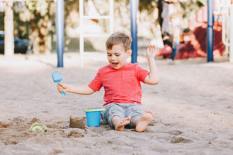 Full length of cute boy playing with sand in playground