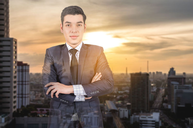 Double exposure of businessman and cityscape against sky during sunset