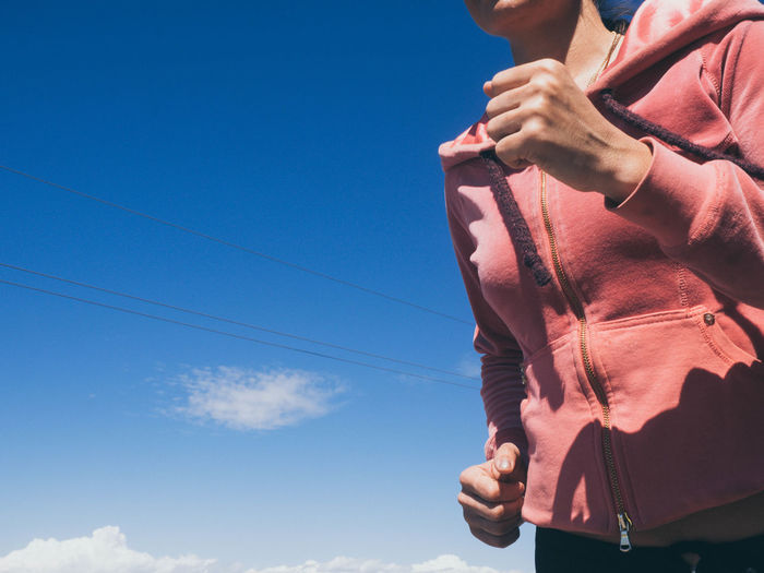Midsection of woman running against blue sky