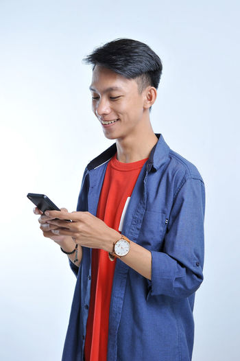 Mid adult man using mobile phone against white background