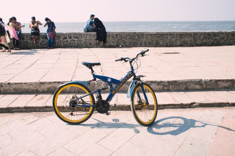 Beach Bicycle Clear Sky Cobblestone Day Horizon Over Water Incidental People Land Vehicle Mode Of Transport Outdoors Sea Shadow Sidewalk Stationary Street Sunlight Transportation Travel Water