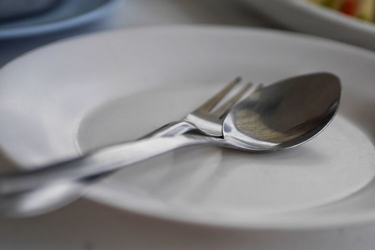 Close-up of eating utensils in plate on table