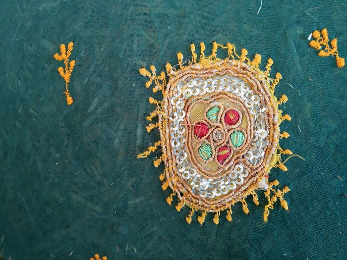 Close-up of embroidery on green fabric