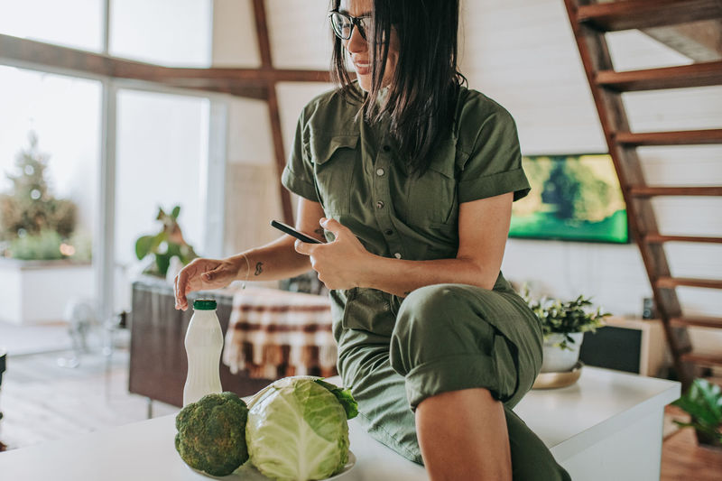 Midsection of woman holding while sitting on table at home