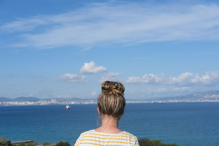 Teenager girl with messy bun looking at the sea. sity and ship on the horizon. sea bay view.