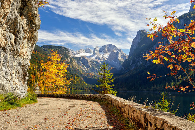 Footpath by mountains against sky during autumn