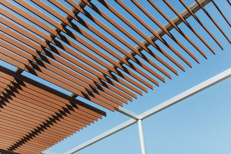 Low angle view of shade structure against clear blue sky
