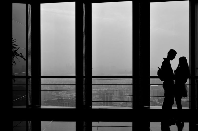 Silhouette man standing by window against sky
