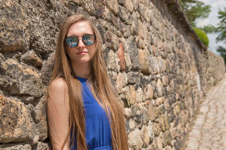 Portrait Of Beautiful Young Woman Standing Against Stone Wall