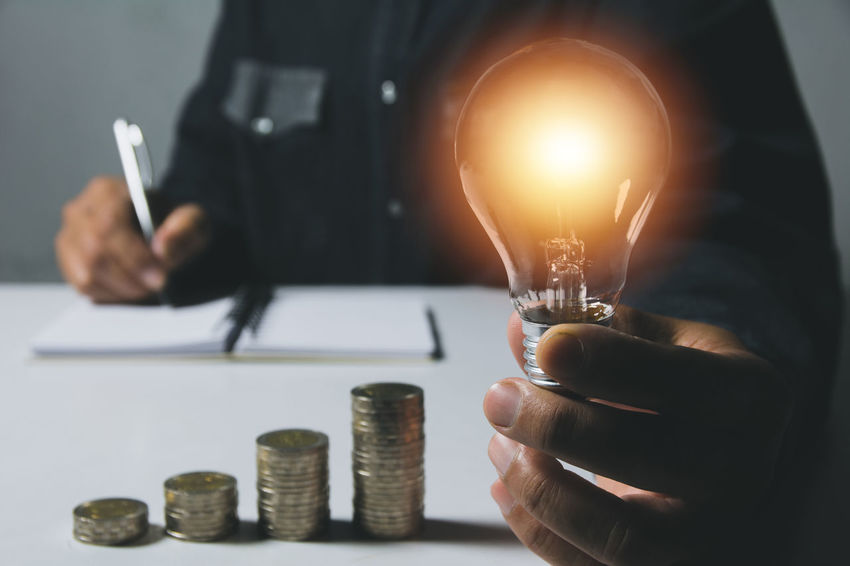 Hand of male holding a light bulb with stack of coins for accounting and creative concept. Finance Human Hand Holding Business Hand Coin One Person Indoors  Human Body Part Currency Men Midsection Light Bulb Close-up Savings Wealth Occupation Real People Focus On Foreground Finger