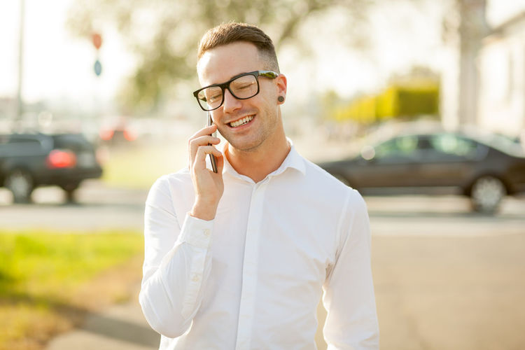 Smiling young man talking on mobile phone while standing in city