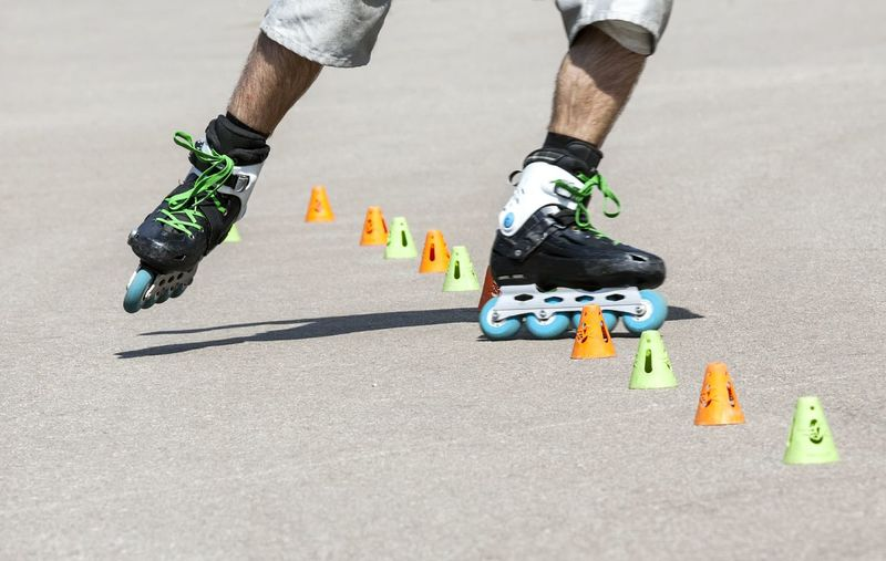 Low Section Of Man Rollerblading Through Cones On Street