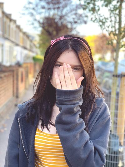 Portrait of teenage girl covering face