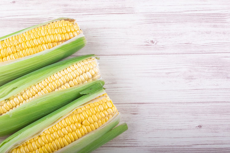 fresh raw sweet corn on the cob kernels over wooden background Food And Drink Food Corn Vegetable Healthy Eating Freshness Still Life Wellbeing Table Yellow No People High Angle View Indoors  Sweetcorn Green Color Corn On The Cob Close-up Wood - Material Raw Food Directly Above Vegetarian Food