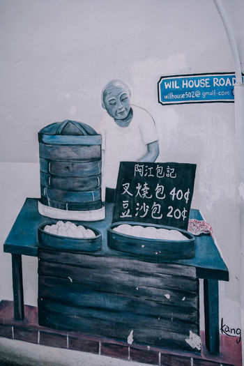 Cool Street art on a wall where a bald man is behind the table selling items. Label Wil House Road along with the email address is written in the blue background with white. ArtWork Artistic Creativity Graffiti Paint Spraying Wall Abstract Art Backdrop Background Blue Brick Building Culture Design Expression Graffitti Grunge Grungy Street Street Art Texture Urban Wallpaper