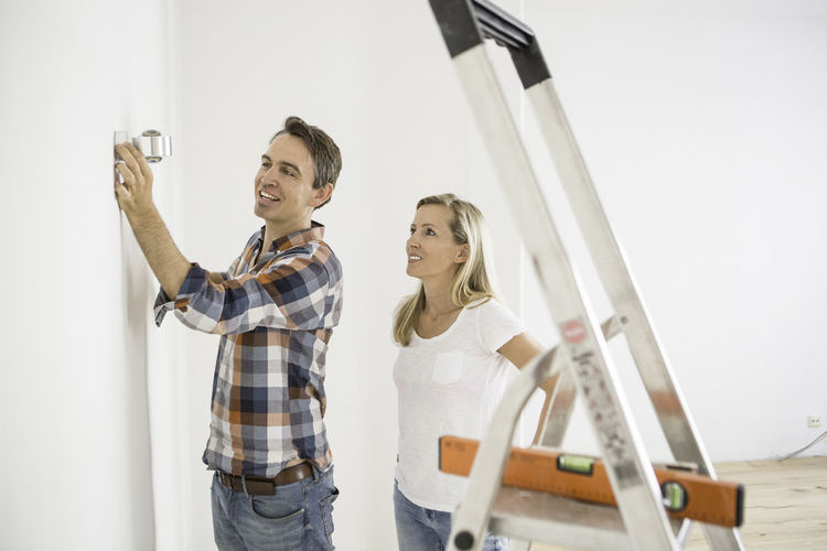 Man and woman fitting a light together on a wall Blond Hair Casual Clothing Day DIY Fitting Lights Ladder Leisure Activity Lifestyles Light Lights Portrait Renovations White