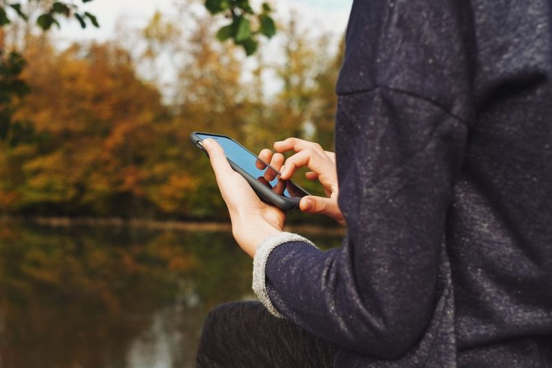 Cropped Image Of Woman Using Smart Phone At Park