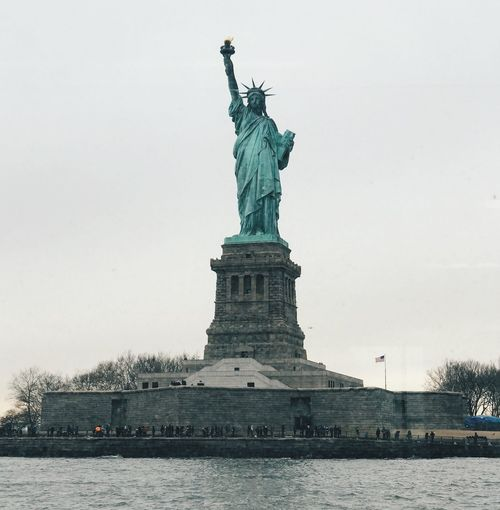 American Flag USA New York City New York Statue Of Liberty Statue Photography Statue Travel Destinations Female Likeness Sculpture Human Representation Tourism Travel Water Monument Architecture Sky Outdoors Day No People Built Structure Clear Sky