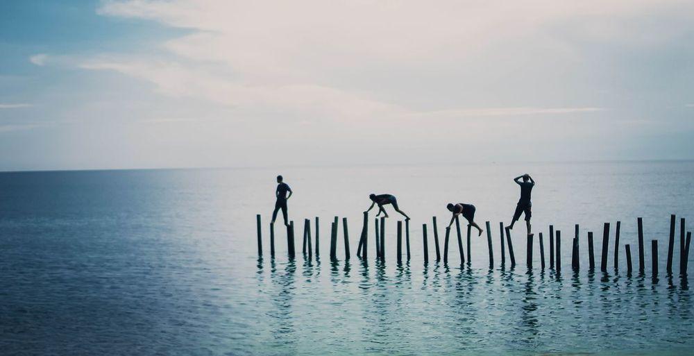 Friends walking on wooden posts in sea