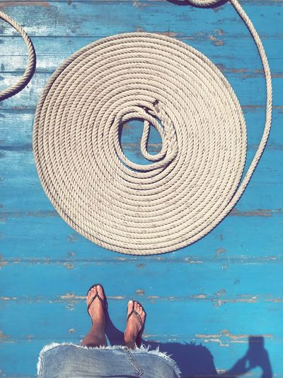 Rope Fresh Casual Travel Perfection Spiral Structure Floor Wood Shapes Shape Balance Woman Feet Flipflops Maritime Blue Boat Ropes Rope Low Section Real People One Person Human Leg Directly Above Lifestyles Human Foot Circle Standing Personal Perspective Geometric Shape