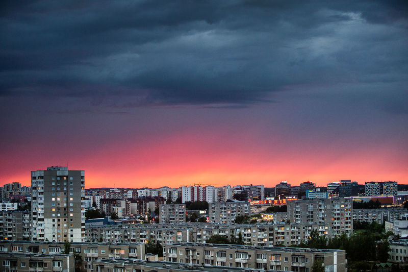 Cityscape against dramatic sky during sunset
