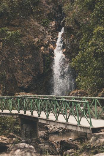 Footbridge against waterfall in forest
