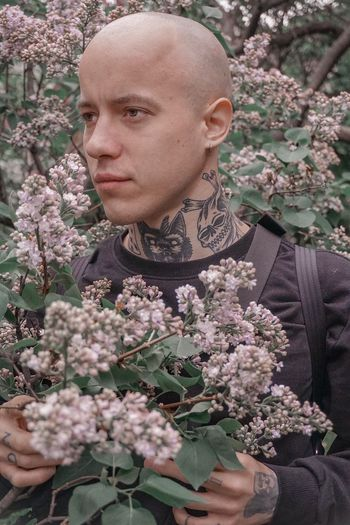 Thoughtful young man amidst flowers