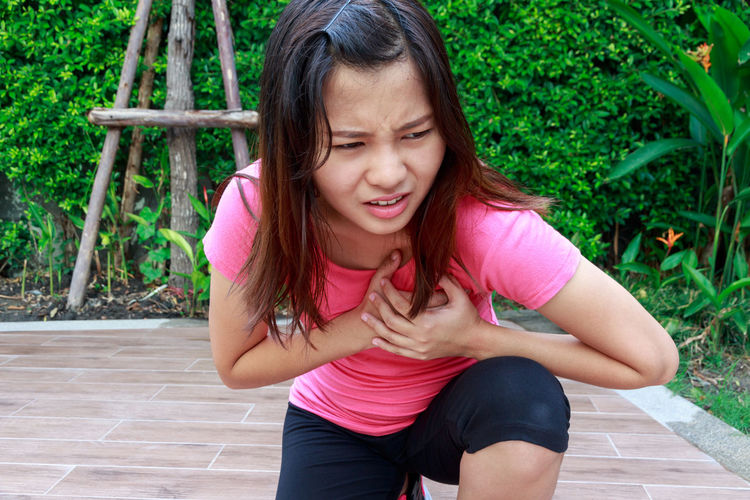 Woman suffering from chest pain kneeling on footpath