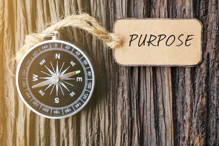 Magnetic Compass and Paper Tag Written With Purpose On Wooden Background. Purpose Travel Close-up Communication Concept Day Magnetic Compass Navigational Compass No People Old-fashioned Paper Texture Tag Text Texture Wooden Background